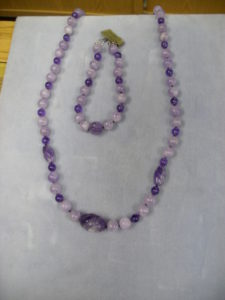 1254-	Multi color Amethysts round bead necklace with a large carved oval dark Amethysts center and two medium sized dark carved ovals.  It has matching bracelet.  Gorgeous colors.